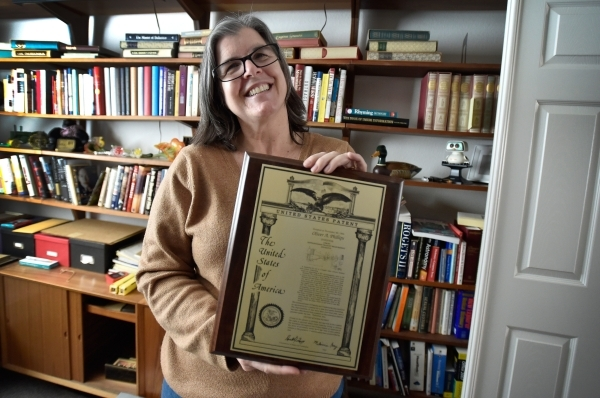 Laura Demetriades displays her father's patent certificate at his Henderson home Tuesday, Feb. 9, 2016. Phillips, 85, died in January from injuries from a beating in his home by a paid escor ...