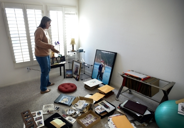 Laura Demetriades stands over family photographs in the Henderson home of her father, Oliver Phillips, Tuesday, Feb. 9, 2016. Phillips, 85, died in January from injuries from a beating in his home ...