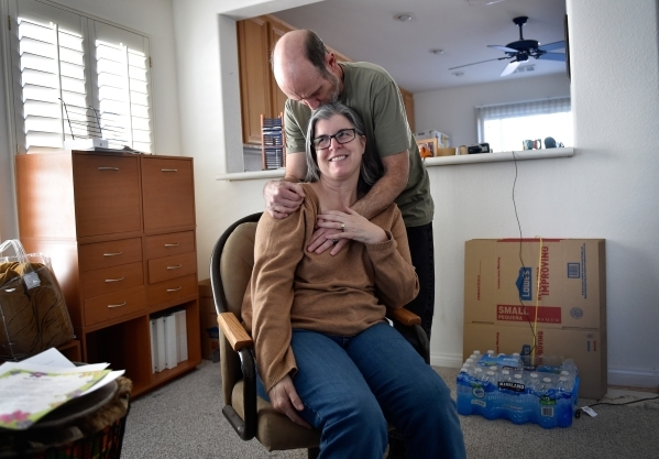 Larry Demetriades comforts his wife, Laura Demetriades, in the Henderson home of her father, Oliver Phillips, Tuesday, Feb. 9, 2016. Phillips, 85, died in January from injuries from a beating in h ...