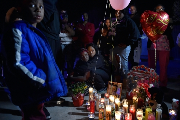 Vickie Davis, center, is held by her sister Nisha Mingo during a candlelight vigil along Thomas Avenue Monday, Feb. 8, 2016, in North Las Vegas. Davis' daughter, 2-year-old Evelyn Green, was ...