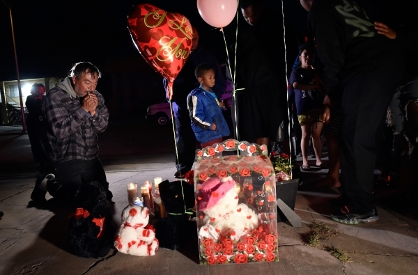 A neighbor prays during a candlelight vigil remembering 2-year-old Evelyn Green along Thomas Avenue Monday, Feb. 8, 2016, in North Las Vegas. Green was killed in a hit and run accident Sunday. Dav ...