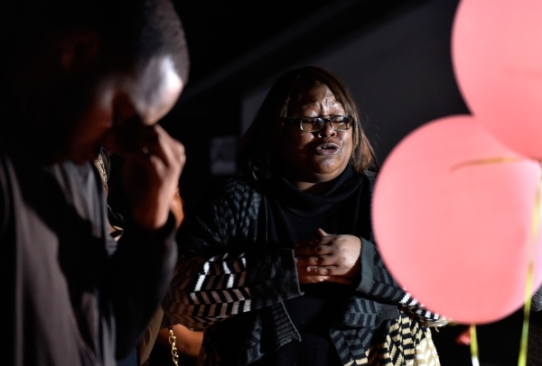 Bonita Harris, right, prays during a candlelight vigil along Thomas Avenue Monday, Feb. 8, 2016, in North Las Vegas. Harris' niece, 2-year-old Evelyn Green, was killed in a hit and run accid ...