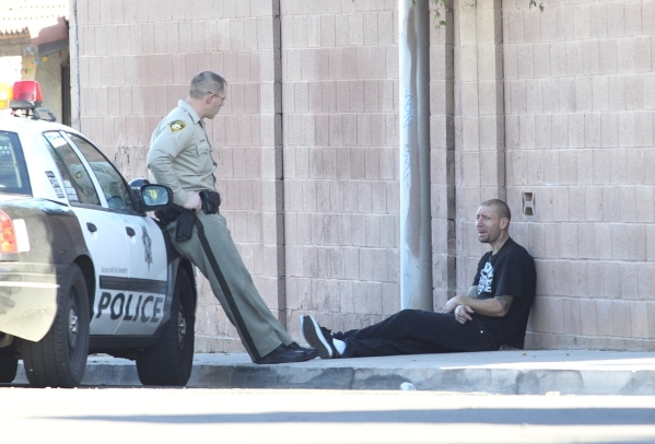 A Las Vegas police officer talks to an unidentified man, near the scene of a shooting at the 2900 block of Kennewick Drive, near the intersection of East Vegas Drive and South Mojave Road, where a ...