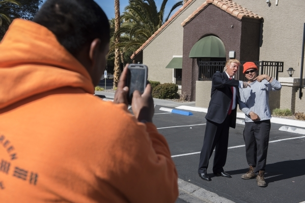 Impersonator Robert S. Ensler, center, poses for a portrait as Donald Trump with Carlos Garcia, right, as Humberto Gomez, left, takes a photo from the Vizcaya clubhouse condominiums in Las Vegas o ...