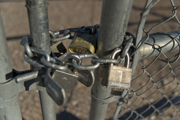Multiple locks hold a gate shut at the end of Losee Road at the northeast end of the 215 beltway on Saturday, Dec. 12, 2015. Much of the land beyond the gate is planned to be developed into The Vi ...