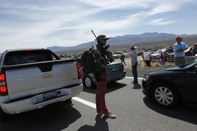 Tyler Lewis, from St. George, Utah, stands in the middle of north bound I-15 with his gun while gathering with other supporters of the Bundy family to challenge the BLM on April 12, 2014. (Jason B ...