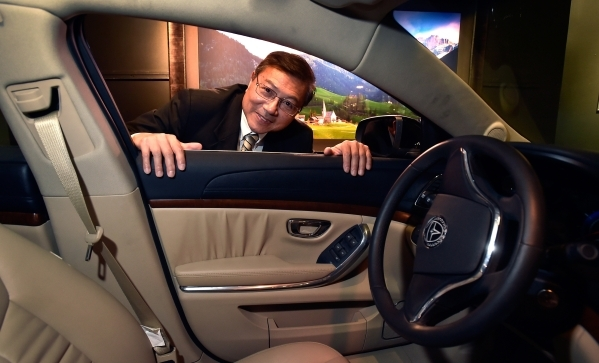 Michael Hu, president and CEO of 2050 Motors peers through the window of his Ibis prototype, an all electric and carbon fiber body automobile, at the William Carr Gallery at Tivoli Village Friday, ...