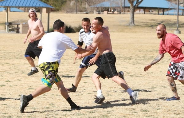 Nicholas Crays, right, tries to avoid a tackle from Angelo DeMunda, left, as they play flag football during a warm Presidents Day at Lorenzi Park on Monday, Feb. 15, 2016, in North Las Vegas. The  ...