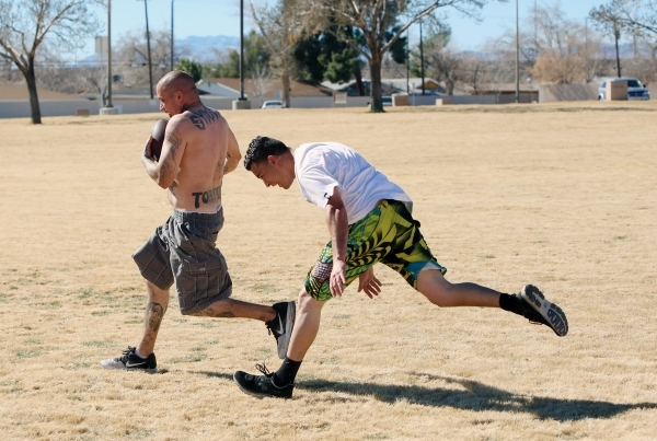 Angelo DeMunda, right, tries but unable to stop Jesse Dunn, left, during their flag football match on a warm Presidents Day at Lorenzi Park on Monday, Feb. 15, 2016, in North Las Vegas. The low ov ...