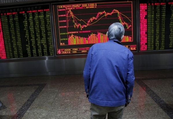 An investor watches an electronic board showing stock information on the first trading day after the week-long Lunar New Year holiday at a brokerage house in Beijing, China, February 15, 2016. (Ki ...