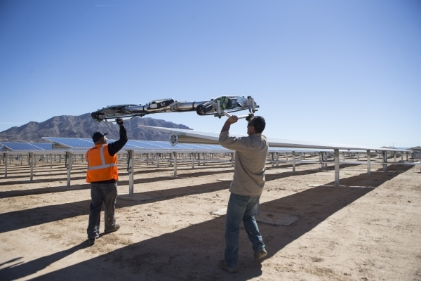 John Gatlin, left, panel washer with Greenbotic, and Oscar Madrigal, field supervisor with SunPower, move a panel washing robot for a demonstration following a dedication ceremony of the completed ...