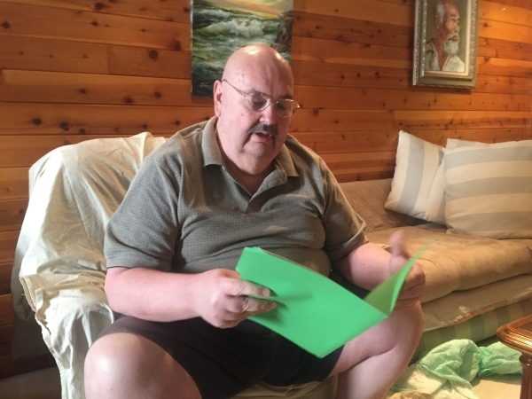 Former Area 51 security officer Fred Dunham reads documents in a file at his Las Vegas home Thursday, Feb. 18, 2016. The file was recently obtained by his compensation claim advocate, Donna Hand,  ...