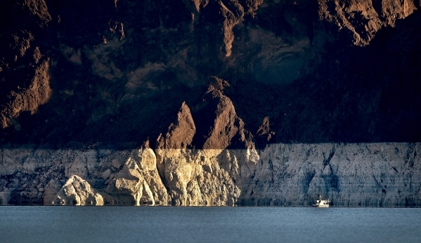 """A small boat is seen at sunset during the annual eagle count at Lake Mead on Tuesday, Jan. 12, 2016. As a long-term drought continues, a white """"bathtub ring"""" on the rocks is formed from  ..."""