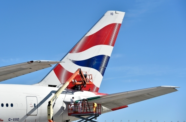 Workers repair a British Airways jet at McCarran International Airport on Tuesday, Feb. 16, 2016, in Las Vegas. The Boeing 777 caught fire after an aborted takeoff last September at the airport. D ...