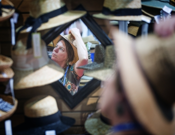 Cathey Wakeman, a retailer from Durango, Col., tries a hat on at the Jeanne Simmons booth during the Men´s Apparel Guild in California show inside the Las Vegas Convention Center on Wednesday, Fe ...
