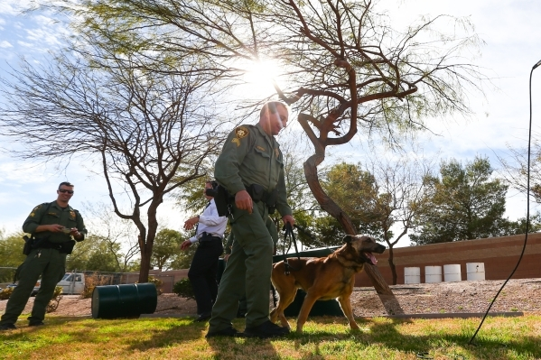 Las Vegas police Sgt. Eric Kerns walks with his partner, K9 officer Nicky, who was attacked by a suspect with a machete on Friday, at South Central Area Command in Las Vegas on Wednesday, Feb. 17, ...