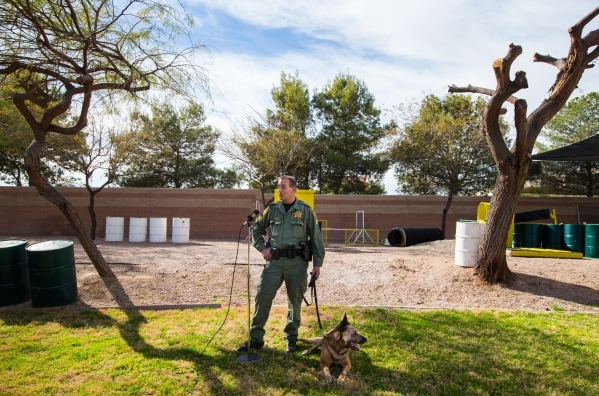Las Vegas police Sgt. Eric Kerns, speaks with reporters alongside his partner, K9 officer Nicky, who was attacked by a suspect with a machete on Friday, at South Central Area Command in Las Vegas  ...