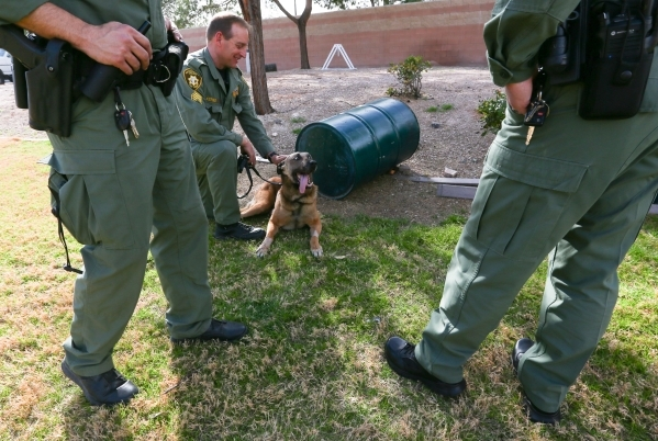 Las Vegas police Sgt. Eric Kerns, center, pets his partner, K9 officer Nicky, who was attacked by a suspect with a machete on Friday, at South Central Area Command in Las Vegas on Wednesday, Feb.  ...