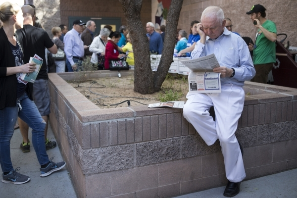 Mike Schaefer reads the newspaper while waiting for shorter lines to register for the Nevada caucus at Becker Middle School on Saturday, Feb. 20, 2016, in Las Vegas. Erik Verduzco/Las Vegas Review ...
