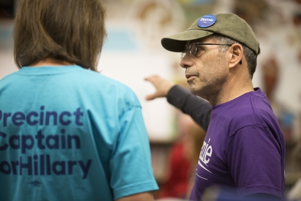 Glenn Elton, a precinct 7685 captain in support of Bernie Sanders, right, speaks with Lynn Susoeff, a precinct 7685 captain in support of Hillary Clinton, during the Democratic caucus at David M.  ...