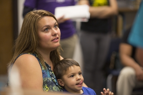 Melissa McGovern, the only undecided caucus goer in precinct 7685, listens to arguments for both candidates while her three-year-old son Tommy sits on her lap during the Democratic caucus at David ...