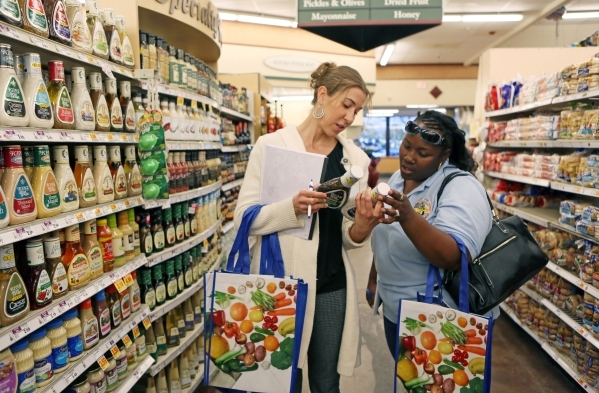 Julie Usdavin, left, a registered dietician with UnitedHealth Group, leads Sparkiel Haley on a health tour of Smith´s grocery store Thursday, Feb. 18, 2016, in Las Vegas. Usdavin offered nutrit ...