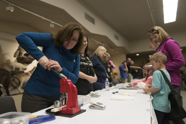 """Jennifer Mihalovich, DNA Technical Leader with the Oakland (Calif.) Police Department , left, creates a button with a custom fingerprint design during the Forensics Day """"CSI-Mini-Camp"""" a ..."""