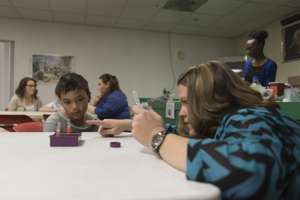 """Curtis Yenkai, 10, left, watches as Krystal May, forensic scientist with the Las Vegas Metro Police Department, extracts DNA from a strawberry during the Forensics Day """"DNA Workshop"""" at  ..."""