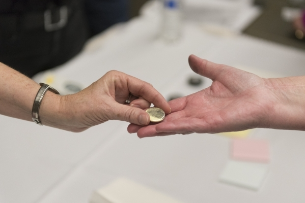"""Patty Jaques, right, is handed a button customized with her fingerprint during the Forensics Day """"CSI-Mini-Camp"""" at the Las Vegas Natural History Museum in Las Vegas Sunday, Feb. 21, 201 ..."""