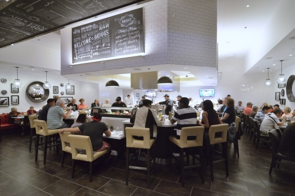 Brigg's Oyster Co. evokes a classic oyster bar, lined with gleaming white subway tile with chalkboard art, and most of the cooking goes on in the center of the room in an area surrounded by  ...