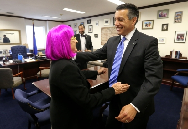 Gov. Brian Sandoval congratulates Sens. Debbie Smith, D-Sparks, and Aaron Ford, D-Las Vegas, following passage of Sandoval's $1.1 billion tax package at the Legislative Building in Carson Ci ...