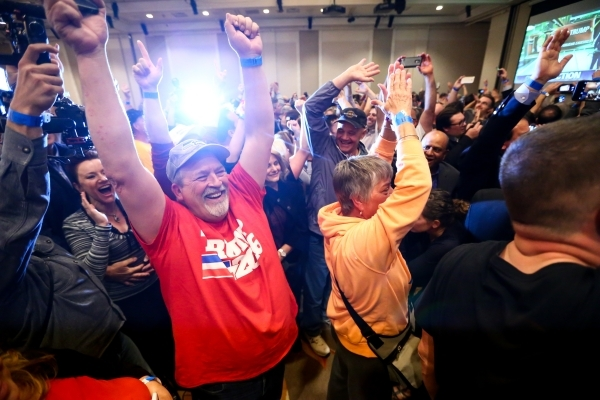 Bob Burns, left, celebrates with others as numbers come in projecting Republican presidential candidate Donald Trump as the winner of the Nevada GOP caucus at Trump's watch party at Treasure ...