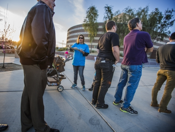 Dee Taylor with Bring Back Solar, tries to get people to sign a roof top solar petition while people stand for the GOP caucus at Canyon Springs High School, 350 E. Alexander Road, in North Las Veg ...