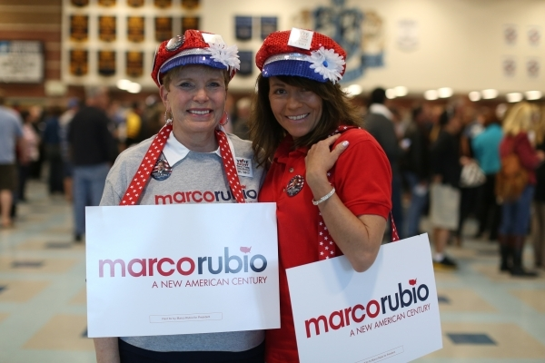 Janet Thietje, left, Stacie Weber don hats and signs in support of presidential candidate Marco Rubio during the 2016 Republican caucus at Centennial High School in Las Vegas on Tuesday, Feb. 23,  ...