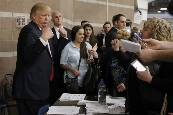 Republican U.S. presidential candidate Donald Trump flexes his muscles as he talks with caucus participants while visiting a Nevada Republican caucus site at Palo Verde High School in Las Vegas, N ...