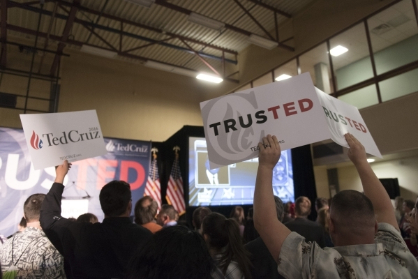 Signs are raised above the crowd at the GOP caucus watch party for presidential candidate Ted Cruz at the Bill & Lillie Heinrich YMCA at 4141 Meadows Lane in Las Vegas Tuesday, Feb. 23, 2016.  ...