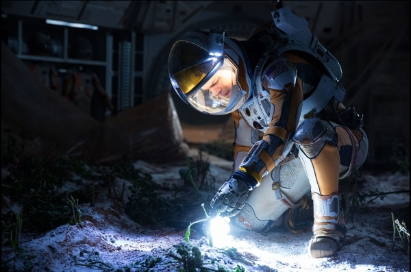 "Matt Damon nurses a potato plant on Mars in a scene from ""The Martian."" (Giles Keyte/Twentieth Century Fox)"