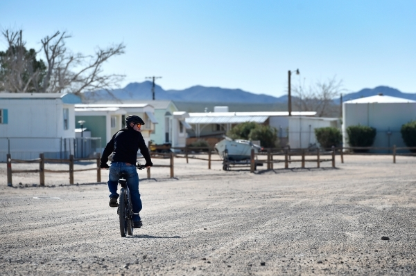 A resident travels along one of the dirt roads on his bicycle Thursday, Feb. 25, 2016, in Cal-Nev-Ari. The small community uses ATVs and bicycles as preferred modes of transportation throughout th ...