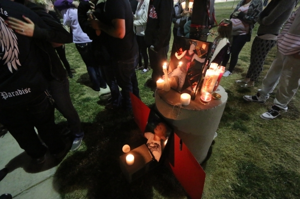 Candles that friends and family lit sit next to photos of Tyler Louis White, who was fatally shot Tuesday, during a candlelight vigil at Desert Breeze Park in Las Vegas on Wednesday, Feb. 24, 2016 ...