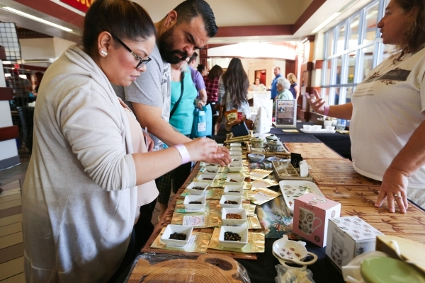 Stephanie Mendoza, left, and her husband Juan Mendoza, center, sample offerings from The Tovah Team during the Southwest Tea Fest at the Downtown 3rd Farmer's Market at in Las Vegas on Satur ...