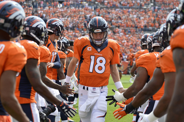 Sep 13, 2015; Denver, CO, USA; Denver Broncos quarterback Peyton Manning (18) high fives teammates prior to their game against the Baltimore Ravens at Sports Authority Field at Mile High. (Ron Che ...