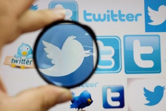 A person holds a magnifying glass over a computer screen displaying Twitter logos, in this picture illustration taken in Skopje September 10, 2013. (Reuters/Ognen Teofilovski)