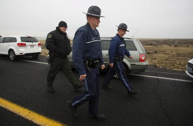 Law enforcement personnel walk along Highway 205, which is closed to most traffic, at the Malheur National Wildlife Refuge outside Burns, Oregon January 28, 2016. U.S. authorities tightened securi ...