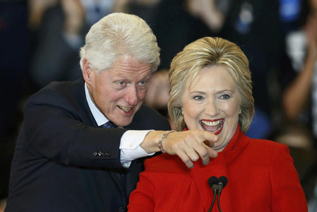 Democratic U.S. presidential candidate Hillary Clinton laughs as she celebrates with her husband, former President Bill Clinton at her caucus night rally in Des Moines, Iowa February 1, 2016.      ...