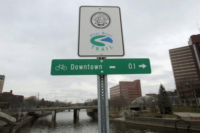 A Flint River sign is seen along the Flint river in Flint, Michigan in this December 16, 2015 file photo.   REUTERS/Rebecca Cook/Files