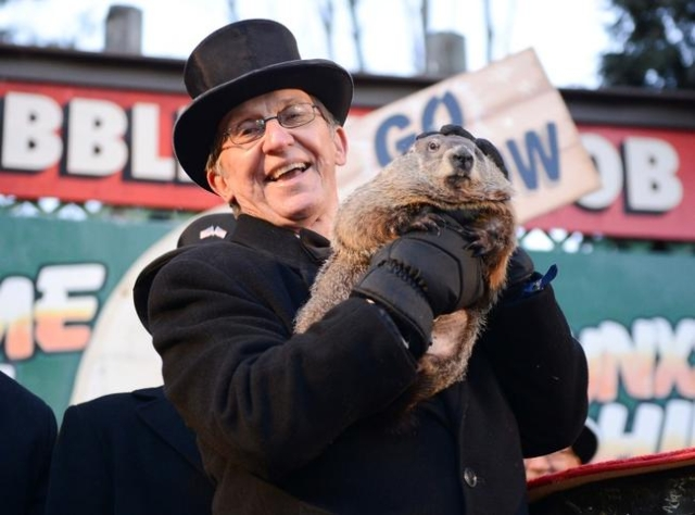 Groundhog co-handler Ron Ploucha holds up groundhog Punxsutawney Phil after Phil's annual weather prediction on Gobbler's Knob on the 130th Groundhog Day in Punxsutawney, Pennsylvania  ...