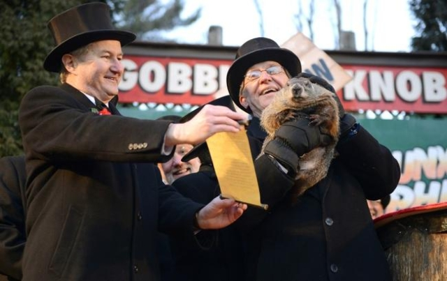 Groundhog Club Vice President Jeff Lundy (L), shares Phil's prediction with co-handler Ron Ploucha on Gobbler's Knob on the 130th Groundhog Day in Punxsutawney, Pennsylvania February 2 ...
