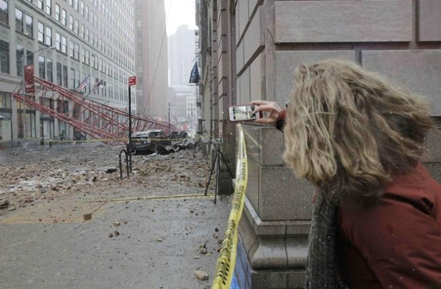A woman photographs a massive construction crane collapse on a street in downtown Manhattan in New York February 5, 2016. The accident killed at least one person and seriously injured two others,  ...