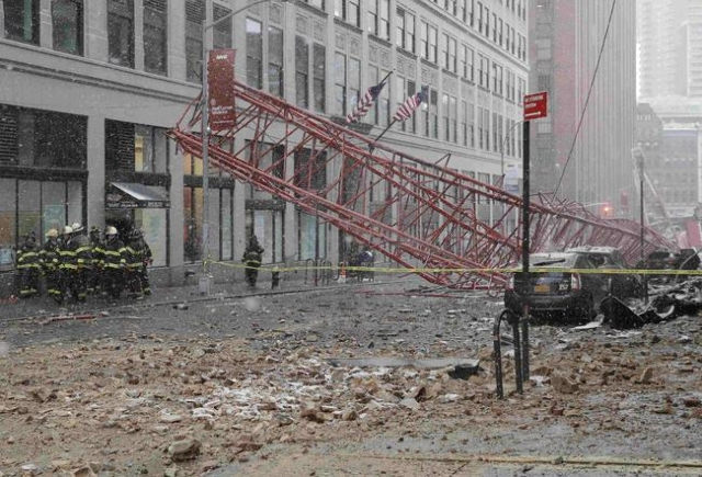 New York City firemen (L) survey a massive construction crane collapse on a street in downtown Manhattan in New York February 5, 2016. The accident killed at least one person and seriously injured ...
