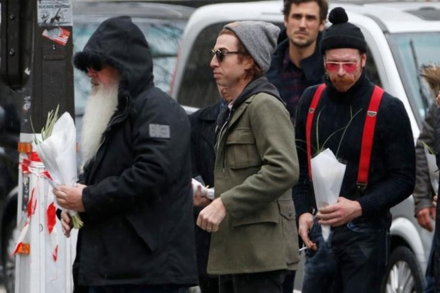 Dave Catching (L), Julian Dorio (C) and Jesse Hughes (R), members of Eagles of Death Metal band, arrive at the Bataclan concert hall to pay tribute to the shooting victims in Paris, France, Decemb ...